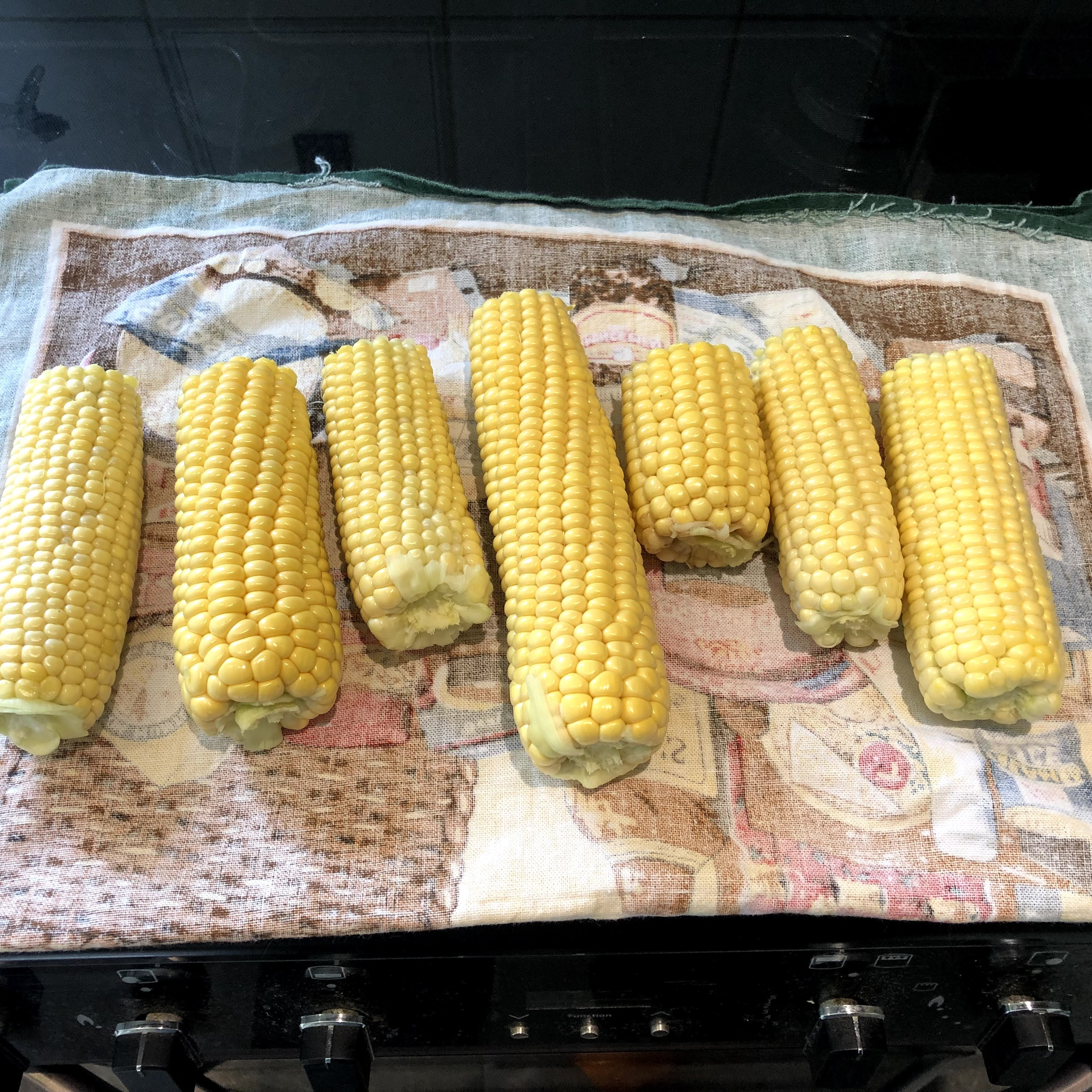 Photograph shows some sweetcorn cobs on a tea towel